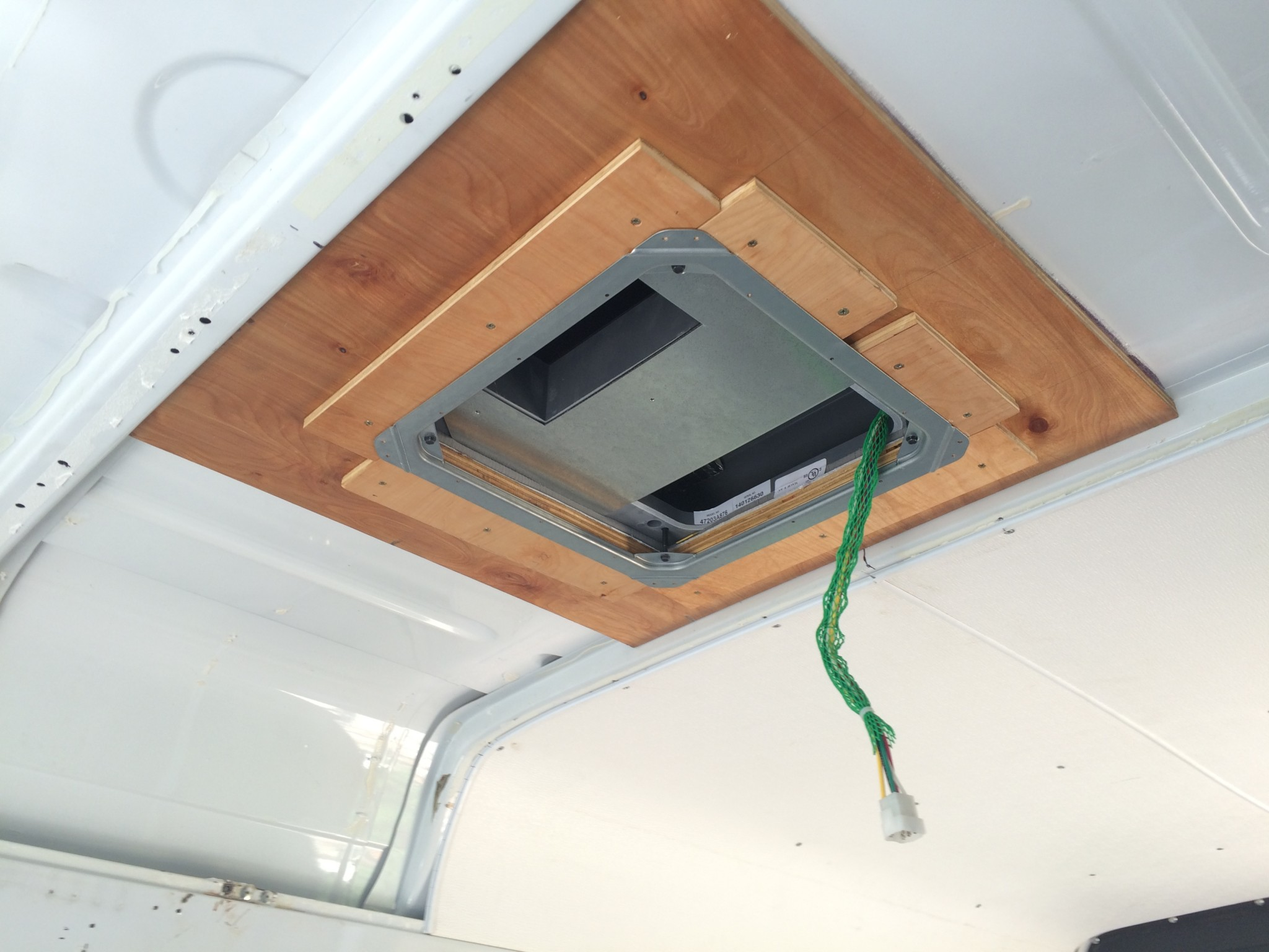 Coleman Mach 8 rooftop unit secured with the bracket and plywood support plate from the inside of the Van